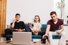 Friends watching a movie on laptop while eating snaks and drinki Stock Photos
