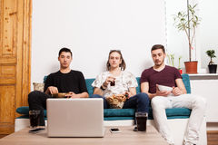 Friends watching a movie on laptop while eating snaks and drinki Royalty Free Stock Photography