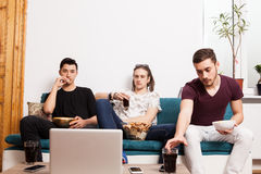 Friends watching a movie on laptop while eating snaks and drinki Stock Image