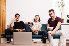 Friends watching a movie on laptop and eating snaks Stock Images