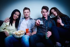 Friends watching movie. Multinational friends watching movie at home royalty free stock image