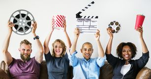 Friends watching movie together indoors. With paper icons Stock Image