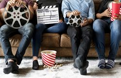 Friends watching movie together sitting on couch stock photos