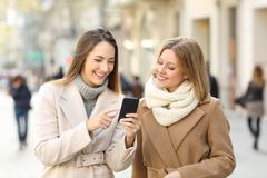 Friends watching phone content in winter on the street. Front view of two friends walking and watching smart phone content in winter on the street Royalty Free Stock Photo
