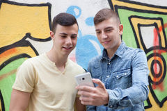 Friends watching the phone in the street. With a painted wall graffiti background Stock Image