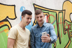 Friends watching the phone in the street. With a painted wall graffiti background Royalty Free Stock Photography
