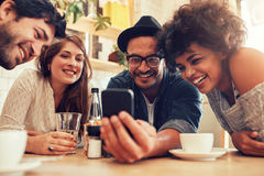 Friends watching photos on mobile phone. Group of friends sitting together in a cafe looking at mobile phone and smiling. Young guy showing something to his Royalty Free Stock Photography