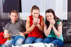 Friends watching a sad movie in TV Royalty Free Stock Photography