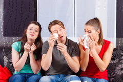 Friends watching a sad movie in TV Stock Images