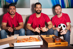 Friends watching a soccer game at night. Portrait of a group of three male friends wearing their soccer team's uniform and watching a game at night with pizza Royalty Free Stock Photo
