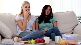 Friends watching something funny on tv Stock Photos