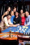 Friends watching the spinning roulette Royalty Free Stock Image