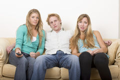 Friends watching TV 2. Friends watching TV on a couch 2 stock photos