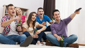 Friends watching TV. Happy friends watching funny movie at home Stock Photos
