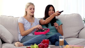 Friends watching TV together while eating chocolates. Sitting on the couch at home stock video