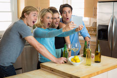 Friends watching videos on a tablet internet device shocked at funny silly laughing viral blog Stock Photo