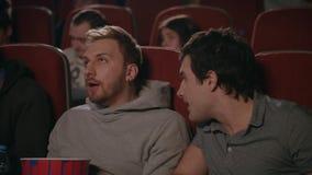 Friends wathcing movie in cinema. Man preventing to friends watching film