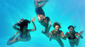 Friends waving at camera underwater in swimming pool together