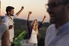 Friends waving with sparklers. Group of friends having fun at an outdoor summertime party, dancing, waving with sparklers and drinking beer stock photos