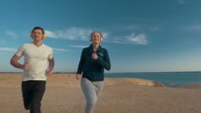 Friends Went for a Run. Steadicam slow motion shot of two friends running alongside the sea. They are moving towards the camera stock video