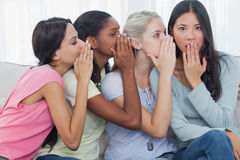 Friends whispering secret to shocked brunette royalty free stock photography