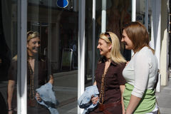 Friends window shopping. Friends looking in shop windows on a sunny afternoon stock photos