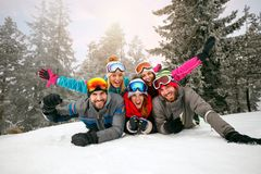 Friends on winter holidays - Skiers lying on snow and having fun Royalty Free Stock Photo