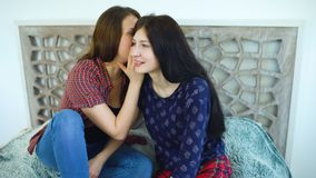 Friends women blonde and brunette sitting bed whispering in ear secrets and smiling. At home Royalty Free Stock Image