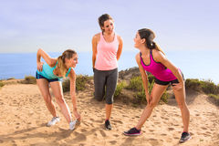 Friends women cute pretty casual conversation athletes stretching in exercise class outdoors before jog and hike on trail path Royalty Free Stock Photography