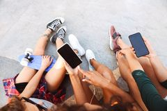 Friends women sitting outdoors using mobile phones. Stock Photo