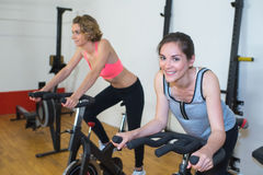 Friends working out cycling in modern fitness club Royalty Free Stock Photos