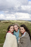 Friends wrapped in blankets in rural field stock image