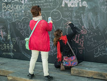 Friends write on chalkboard at Berges de Seine, Paris, France Royalty Free Stock Photography