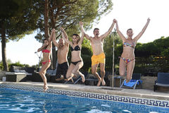 Friends young happy attractive men women in bikini jumping in the air to hotel swimming pool Stock Photos