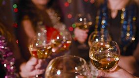 Young women colleagues at a corporate or Christmas party clink glasses of champagne. Friends or young women colleagues at a corporate or Christmas party clink stock video footage