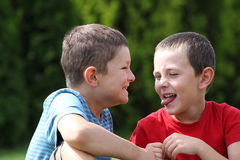 Friendship. Portrait of two boys, siblings, brothers and best friends giggling and making faces Stock Images