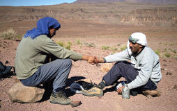 Friendship. Guide and cook work together to get you a comfortable trek in Djebel Sahro mountains stock photo