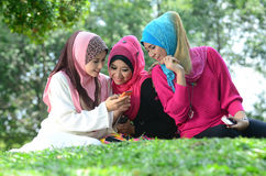 Friendship. Young muslim women in head scarf meet friends and using phone in the park Royalty Free Stock Photos