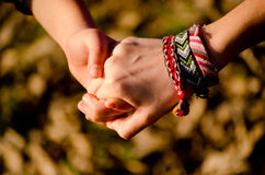 Friendship. Two girls shaking hands and wear friendship bracelets Royalty Free Stock Images