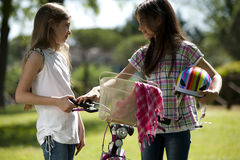 Friendship. Two little girls with bike outdoors Royalty Free Stock Photography