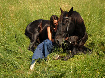 Friendship. Bettween a teenager and a black stallion Stock Photography