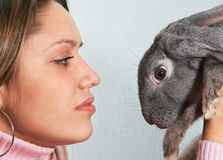 Friendship. Close-up portrait girl holding rabbit on hand Stock Images