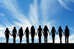 Friendship. Silhouette of ten young women, walking hand in hand Royalty Free Stock Photos