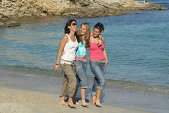 Friendship. Three friends happily walking along waters edge Royalty Free Stock Image