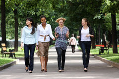 Friendship. Four young women walking in the park Stock Photos