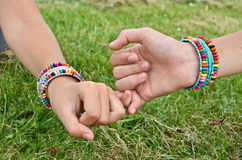 Friendship bracelets. Two girls shaking hands and wear friendship bracelets Stock Photo