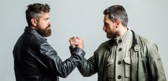 Friendship of brutal guys. Leadership concept. True friendship of mature friends. Male friendship. Brutal bearded men. Wear leather jackets shaking hands. Real stock image