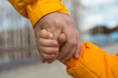 Friendship. The child holding the hand of man. Photo close up Stock Image