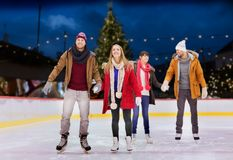 Happy friends on christmas skating rink Stock Images