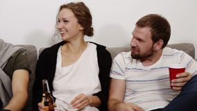 Friendship, communication, party time - cheerful caucasian friends talking, having fun, sitting on couch indoors and. Laughing, eating, drinking. Close up stock footage